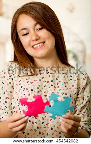 Headshot charming brunette woman holding up big puzzle pieces in pink and blue, smiling happily to camera, white studio background - stock photo