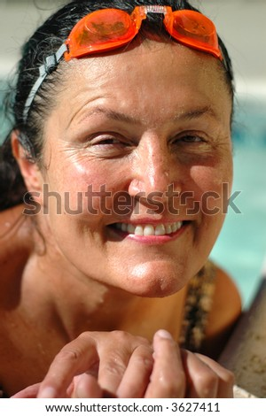 Headshot of a gorgeous woman in her late fifties working out in the pool - stock photo