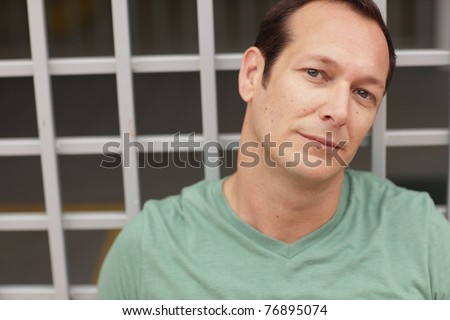 Headshot of a man tilting his head sideways - stock photo