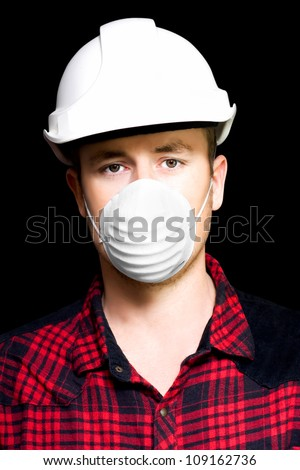 Headshot of a serious young male artisan wearing a hard hat and dust mask for particle inhalation protection on a black studio background - stock photo