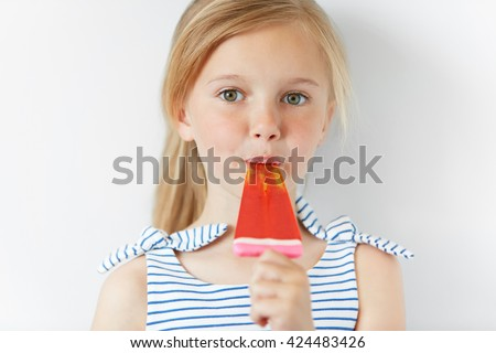 Headshot of adorable preschool female child holding popsicle and looking at the camera. Cute blonde little girl licking fruit ice-cream standing against white studio wall. People and lifestyle concept - stock photo