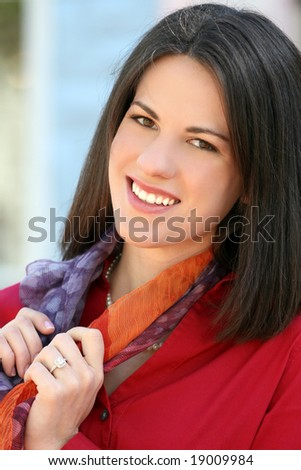 Headshot of an attractive business, corporate female in a red shirt outdoors. Suitable for a variety of commercial, finance and business themes.