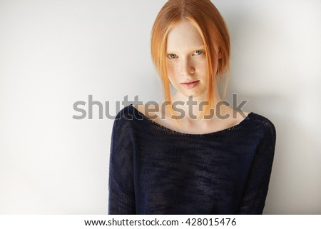 Headshot of attractive student girl with red hair, blue eyes and perfect healthy freckled skin, wearing white top, looking and smiling at the camera, isolated against white concrete wall background  - stock photo