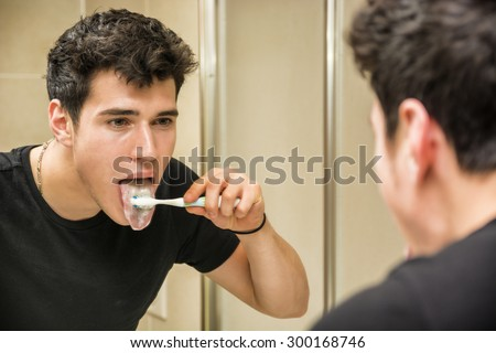 Headshot of attractive young man brushing teeth and cleaning tongue with toothbrush, looking at himself in mirror - stock photo