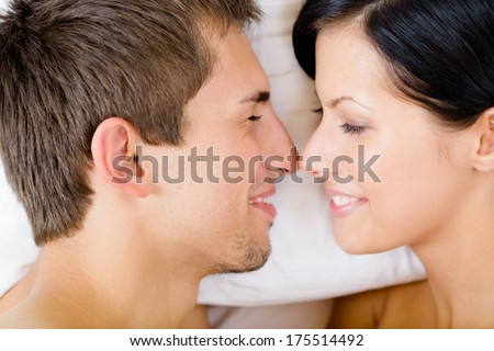 Headshot of couple lying in bed, top view. Concept of love and affection