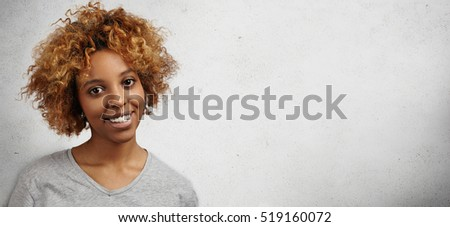 Headshot of pretty African female customer or student with Afro hairstyle and facial piercing looking happy and cheerful after shopping or getting excellent mark at university. Positive human emotions