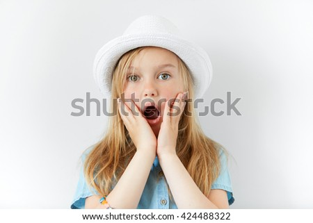 Headshot of pretty surprised little girl wearing white hat and denim shirt with hands on cheeks looking at the camera with astonished or shocked expression, mouth wide open. Human facial expressions  - stock photo