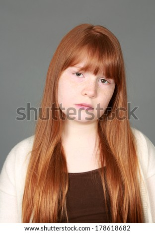 headshot of sad preteen redhead girl with freckles - stock photo