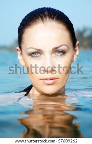 Headshot of the pretty woman in the water at the summer beach. Vertical photo with natural colors and light