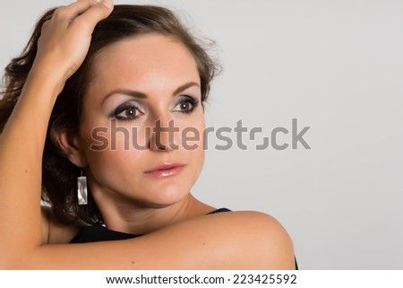 Headshot portrait of a beautiful woman on the gray wall. Woman 36 years old. - stock photo
