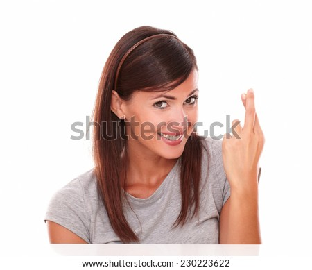 Headshot portrait of adult single female making a wish with luck sign while smiling and looking at camera on isolated studio - stock photo