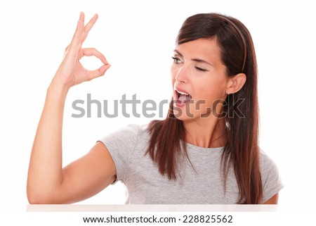 Headshot portrait of beautiful young brunette with ok sign winking and looking to her right on isolated studio - stock photo