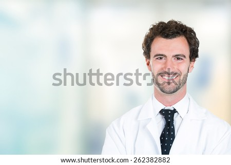 Headshot portrait of friendly young male doctor smiling standing in hospital hallway clinic office windows background  - stock photo