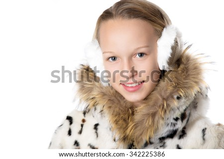 Headshot portrait of happy funny beautiful casual teenage girl wearing winter coat and earmuffs, looking at camera with cheerful expression, studio image, white background - stock photo