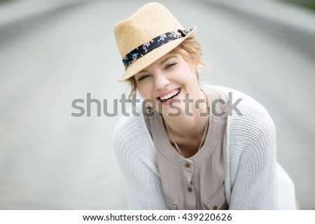 Headshot portrait of laughing beautiful caucasian woman wearing casual clothing. Young female standing on the street in summer and looking at camera. Attractive model posing with cheerful expression - stock photo
