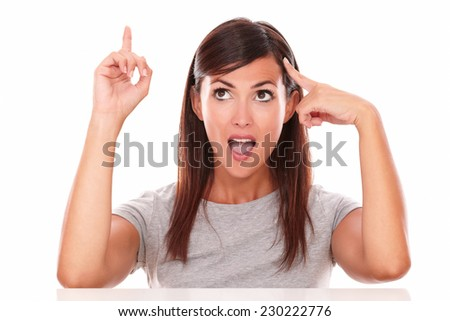 Headshot portrait of surprised hispanic lady pointing her head while pointing and looking up on isolated studio - copyspace - stock photo