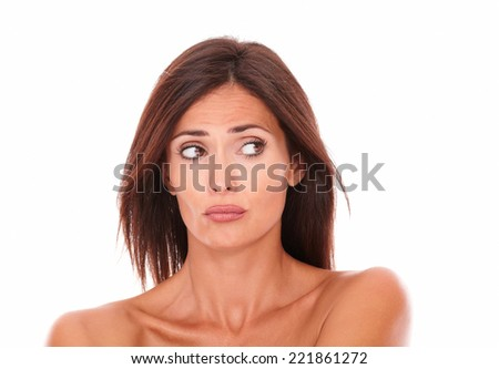 Headshot portrait of unsmiling latin woman with nude shoulders looking to her left on isolated white background - copyspace - stock photo