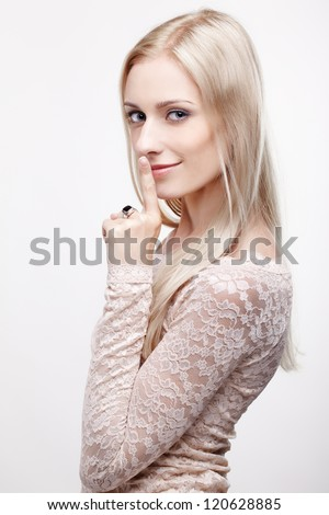 headshot portrait of young beautiful blonde woman asking to be silent