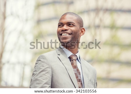 Headshot portrait of young professional man smiling laughing isolated on outside outdoors corporate office background. Positive human emotions feelings facial expressions  - stock photo