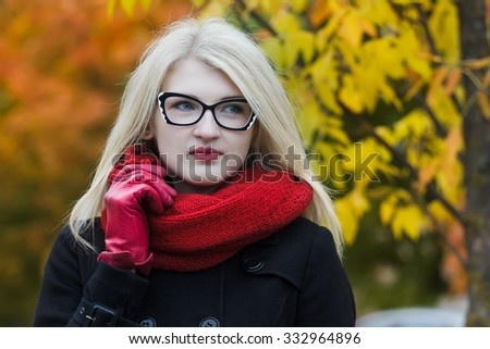 Headshot portrait of young woman is wearing cat eye glasses and holding red knitted scarf with one arm in red leather glove - stock photo