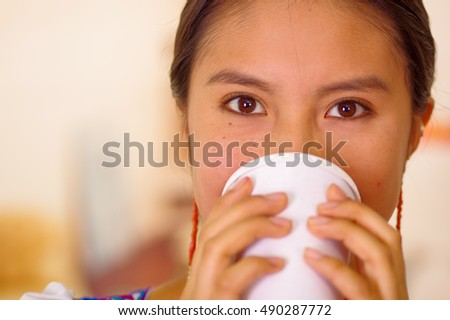 Headshot pretty young woman wearing traditional andean blouse, drinking coffee from white mug