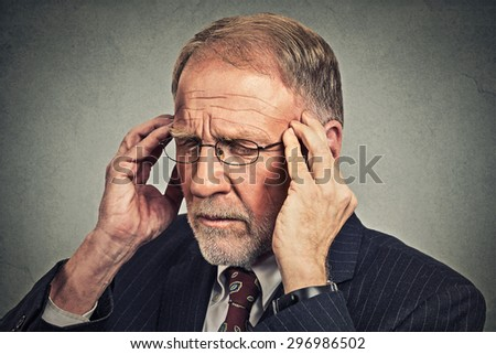 Headshot stressed senior man looking down sad depressed, alone, disappointed, gloomy, hands on head isolated on gray wall background. Human emotion face expression reaction  - stock photo