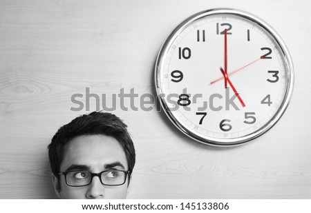 Headshot young businessman looking at clock on wall in office - stock photo