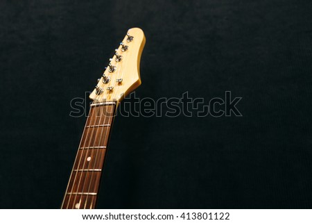 Headstock of the six string electric guitar top view in sound recording studio. Headstock of electric guitar  flat lay on black background. Musical instrument closeup with free space. - stock photo