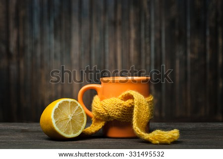 Healing glass of tea in a scarf and a lemon on a wooden background - stock photo