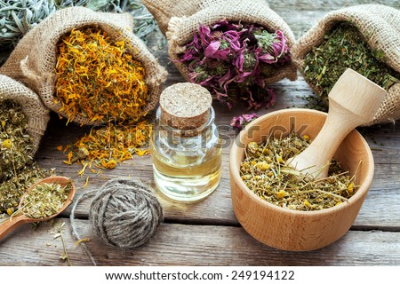 Healing herbs in hessian bags, mortar with chamomile and essential oil on wooden table, herbal medicine. - stock photo