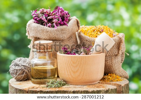 Healing herbs in hessian bags, wooden mortar with coneflowers and essential oil on wooden stump outdoors, herbal medicine. - stock photo