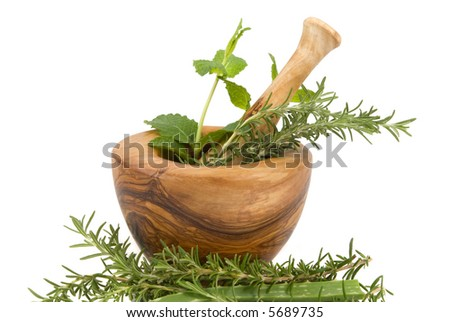 Healing herbs on white background (hand carved olive tree mortar and pestle)