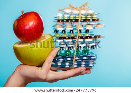 Health and balanced diet concept. Choice between two sources of vitamins - pills or fruits. Closeup female hand holding stack of drugs apple and grapefruit on blue. - stock photo