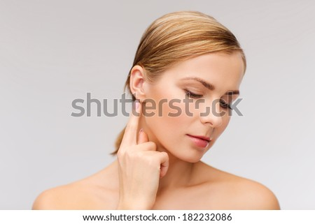 health and beauty concept - face of beautiful woman touching her ear - stock photo
