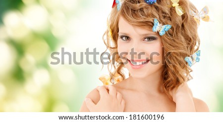 health and beauty concept - happy teenage girl with butterflies in hair