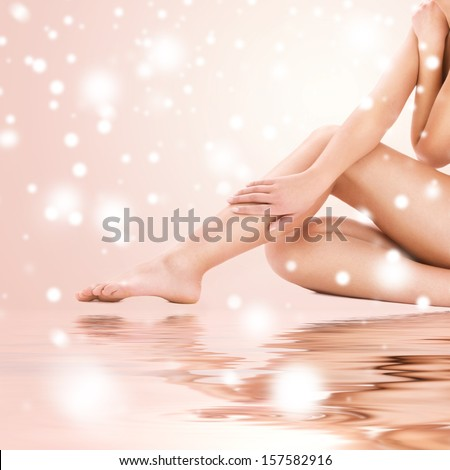 health and beauty concept - healthy naked woman legs over beige background - stock photo