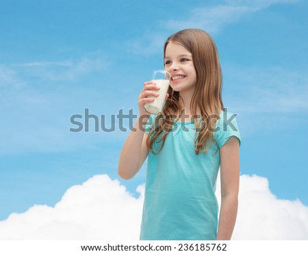 health and beauty concept - smiling little girl drinking milk out of glass - stock photo