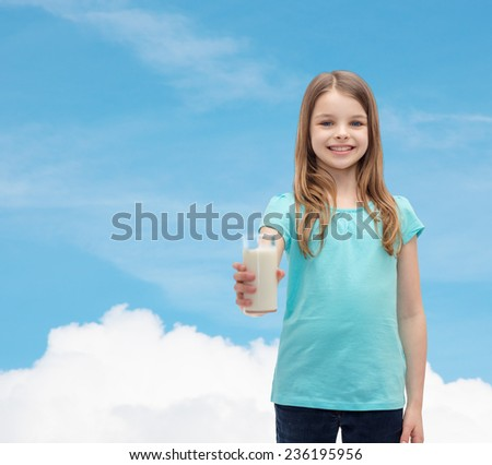 health and beauty concept - smiling little girl giving glass of milk - stock photo