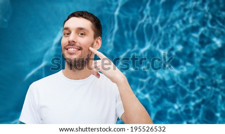 health and beauty concept - smiling young handsome man pointing to cheek - stock photo