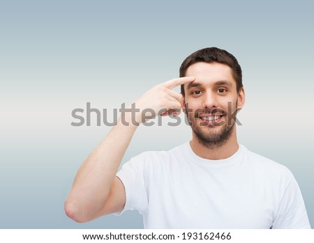 health and beauty concept - smiling young handsome man pointing to forehead - stock photo