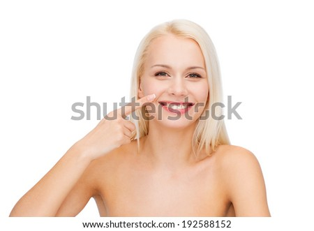 health and beauty concept - smiling young woman pointing to her nose - stock photo