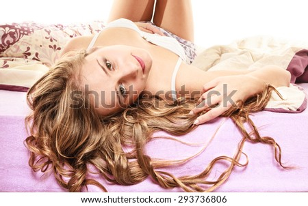 Health and beauty concept. Young lovely woman long curly hair relaxing on her bed at morning