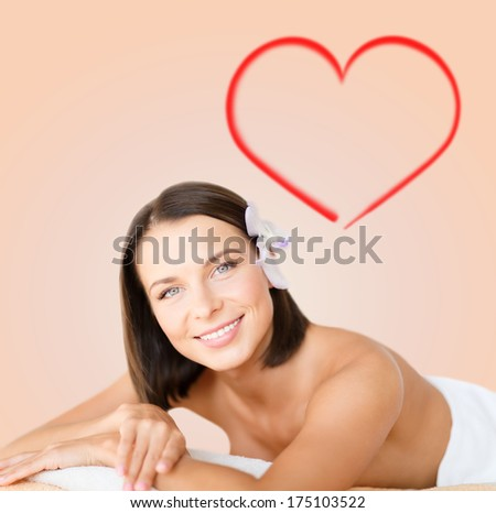 health and beauty, resort and relaxation concept - beautiful woman with flower in her hair in spa salon lying on the massage desk - stock photo