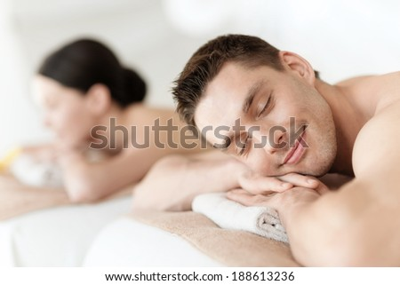 health and beauty, resort and relaxation concept - couple in spa salon lying on the massage desks - stock photo