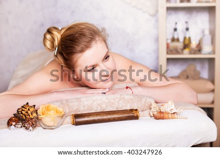 health and beauty, resort and relaxation concept - smiling  caucasian woman  in spa salon lying on the massage desk. Closeup face - stock photo
