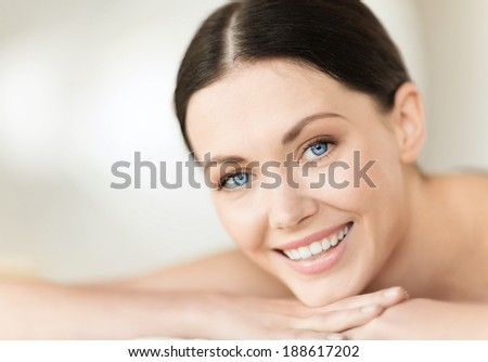 health and beauty, resort and relaxation concept - woman in spa salon lying on the massage desk - stock photo