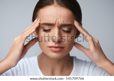 Health And Pain. Stressed Exhausted Young Woman Having Strong Tension Headache. Closeup Portrait Of Beautiful Sick Girl Suffering From Head Migraine, Feeling Pressure And Stress. High Resolution Image