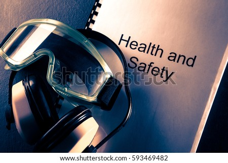 Health and safety document with earphones and goggles