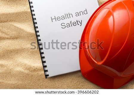 Health and safety register with helmet on sand - stock photo