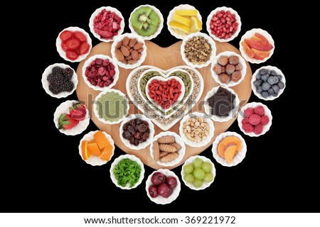 Health and superfood selection in heart and round shaped porcelain bowls on a wooden board over black background with copy space. High in vitamins and antioxidants. - stock photo